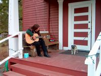 A patron gets musical on the Schoolhouse porch